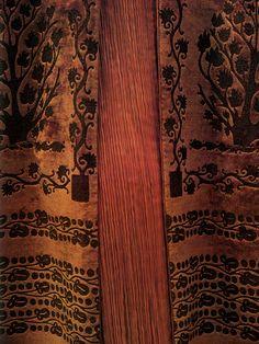 Detail of Fortuny Delphos pleats beneath a silk velvet coat stenciled in gold with motifs reinterpreting Coptic and Cretan designs.