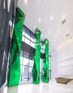 Fly Condos | Columns // this glass and stone tower features an impressive triple-height lobby supported by three custom engineered columns clad with vibrant green, multi-faceted glass // Commercial Mirror Lobby Condo Studio Munge