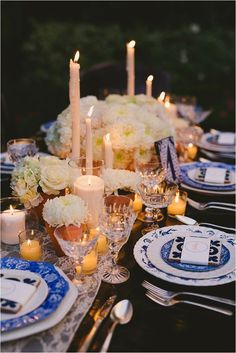 Candlelit tablescape with terracotta planters and white & ivory flowers.: