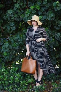 Blogger Girl With Curves wears a summery black and white striped wrap shirtdress with a tan leather tote, espadrilles, and a floppy straw hat