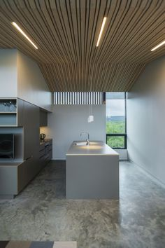 A modern version of the traditional Icelandic turf house, this vacation home blends into the landscape. It has three bedrooms in 1,109 sq ft. | www.facebook.com/SmallHouseBliss  love the lights in the slat ceiling
