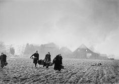 GERMANY. 1945. Near Wesel. German farmers fleeing their burning houses. By Robert Capa.