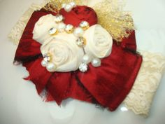 Stunning Dark Red and Ivory Dupioni Silk bow adorned with Ivory and Dark Red handmade rolled rosettes and gold tulle. High quality rhinestone and pearl clusters and will be attached to an Ivory lace headband! AVAILABLE IN ALL WHITE, ALL IVORY, AND ALL PINK. ANY COLOR BOW WILL HAVE GOLD TULLE BOW ATTACHED!!!! SELECT COLOR AND SIZE AT CHECKOUT.....  Your headband will be shipped in a sturdy mailing box to prevent crushing.  THANKS SO MUCH FOR SHOPPING LE PETITE JARDIN...