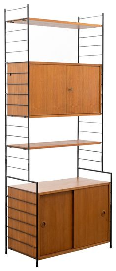 """<p>Bookcase string in teak from the 60s. Manufacturer: WHB.<span style=""""font-family: Arial; font-size: 12px; font-style: normal;"""">Teak veneered surfaces. Two black metal ladders, one container with sliding doors, one container with lockable double door and two shelves. Good condition with small traces of use.</span></p>"""