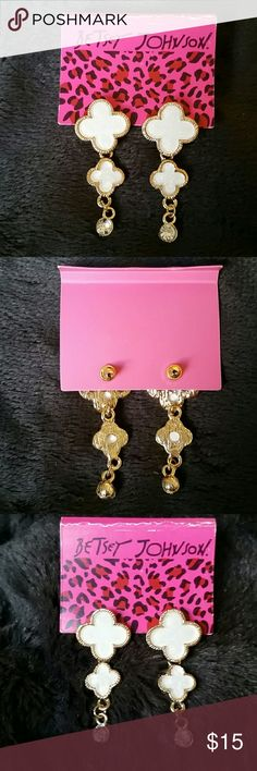 """NWT Betsey Johnson White Sparkle Flower Earrings New with tags Betsey Johnson earrings. They are shiny gold tone metal with two 4 petal resin clover flower cross shapes that are super sparkly white and crystal rhinestone drops at the bottom. One of the smaller flowers looks like it wasn't set in properly, and doesn't sit flush, but firmly in place (shown in pics) - my price reflects this mfg flaw. The tag card also shows wear at the top crease. They are 1.75"""".  Thank you for checking out my…"""