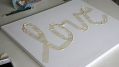 "canvas painting ideas | We began by ""writing"" a word on the canvas with masking tape."