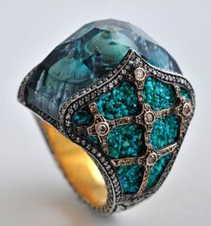 """Featuring two of the Turkish master-jeweller's signature techniques - intaglio carving and micro-mosaic - the queen's palace rises majestically beneath blue tourmaline, its domes echoed in the dramatic setting of turquoise tesserae, diamonds, blackened silver and gold. Describing his jewellery as """"Byzantine empire meets Alice in Wonderland"""", Sevan Biçakçi is famously secretive about the techniques used to create his fantastical pieces."""