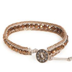 Deze geraffineerde armband is een kunstwerkje op zich. Facet kralen in de kleur brons bevestigd tussen beige waxkoord met aan de uiteinden een goudkleurige schakelcollier. De mooie knoopsluiting met Swarovski kristallen zorgen voor een sportieve afwerking.