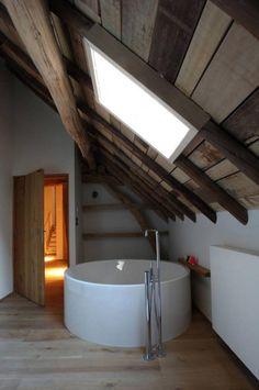 poutre en bois, baignoire ronde au-dessous de poutres apparentes