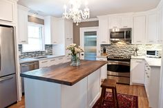 Complete renovation of kitchen. Custom stark white cabinets, gray/blue/white glass backsplash(Lowes), Silestone countertops, walnut butcher block on the island(custom), reed glass door(Lowe's) and crystal chandelier for flair (antique store).