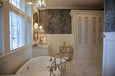 Geneva Cabinet Company   Lake Geneva, Wisconsin   Traditional Retreat Master Bath Luxury detailing in a bath using cabinetry from Plato Woodworking, a built in armoire has glass door with x mullions and detailed with crown molding, a free standing tub with hand held shower plumbing fixtures and  his and her matching vanities.  Damask wallpaper is above wainscot paneled walls.#cabinets #bathrooms #bathroomideas #bathroomdesign #bathroomcabinetry