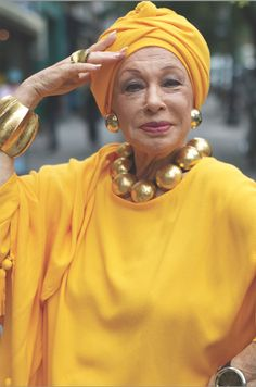 Yellow and gold, drapey with a turban and a big gold ball necklace.