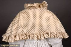 BROWN ON WHITE CALICO PELERINE, 1820s Cotton printed with sprigged diamonds, piped and ruffled band collar and hem trim.