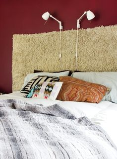 A bed with a shaggy hanging rug as a headboard, a fabulous gray fur blanket, all in front of a perfect deep wine colored wall paint.