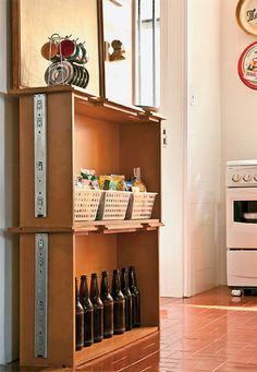 Empilhadas no chão rente à parede, duas gavetas de uma cama sem uso se tornaram prateleiras para garrafas e cestos.