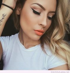 Black liner, orange lips and a simple white tee