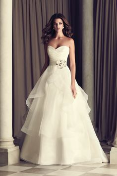 Italian Taffeta and Organza bridal gown. Strapless cross-over pleated Taffeta bodice. Removable Italian Taffeta belt with side beaded flower embellishment at natural waist. Full tiered organza skirt with mohair detailed edging. Chapel Train. Style 4465. #PalomaBlanca #PalomaGown Paloma Blanca Wedding Gown