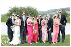 The bride, bridesmaids and groomsmen.  The dresses were all a shade of pink at Duncan and Sarah's Backyard Wedding in Godmersham, Kent
