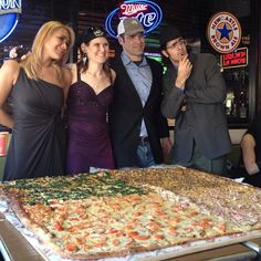 """This foursome is about to try and eat this pizza (54""""x54"""") in, gulp, under an hour. (at Big Mama's And Papa's Pizzeria)"""
