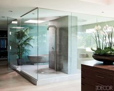 The serene master bath in filmmaker Michael Bay's Miami Beach home is sheathed in etched-stone tiles; the bathtub is cast concrete, and the shower fittings are by Boffi. Tour this home.