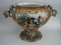 """This is an Antique Mettlach Pottery Punch Bowl or Tureen marked with the impressed Castle mark and the number """" 2088 """" .The colors are vibrant and the features of the subjects are crisp. The piece is particularly beautiful because of the Heavy Gold decoration on many of the raised embellishments. It measures a very impressive 11 1/2 inches tall by 17 inches wide at the Sea Serpent shaped handles ."""