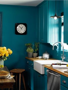 In this photo: Ikea's white farmhouse sink pops against Varsity Blues by Benjamin Moore that covers the walls, cabinets, and trim. Sarah bought the clock at the Hudson, New York, shop Rural Residence. Read more: Creative Home Decorating Ideas - Restored Home Decor - Country Living