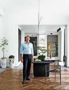Rodriguez stands in the entrance hall with artworks by, from left, Adam McEwen, Dan Colen, and Theaster Gates; the light fixture is by Michael Anastassiades, the table is by B&B Italia, and the corner chair is by Rick Owens.