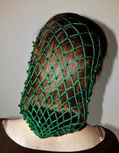 Green crochet hair net interspersed with glass beads.
