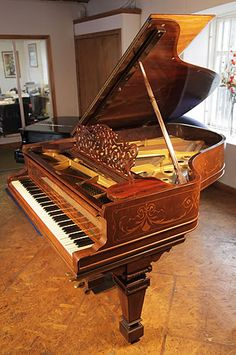A 1900, Steinway Model A grand piano with a rosewood case. Cabinet inlaid with satinwood stringing, swags and scrolls  at Besbrode Pianos