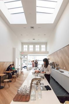 A curved serving counter clad with a honeycomb pattern of white tiles occupies the front space of this cafe in San Francisco, California.