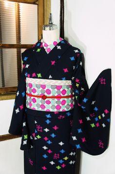 ほとんど黒に近いミッドナイトネイビーの地に、青、ピンク、黄色、緑のビビッドカラーの十字と井筒の絣模様が織りと染めでデザインされたウールの単着物です。