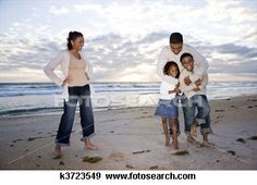 Happy African-American family of four on beach View Large Photo Image