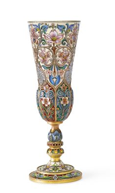 A Russian gilded silver and shaded enamel champagne flute, Fedor Rückert, Moscow, 1899-1908, of tapering shape, the bottom of the goblet gadrooned and decorated with applied cables, the stem with two knops, the body enameled with brightly colored, stylized foliage against a cream ground, set on a spreading foot similarly enameled.