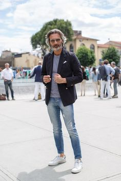 This combination of a black cotton blazer and blue ripped skinny jeans is perfect for a night out or smart-casual occasions. Mix things up by wearing white low top sneakers. Shop this look on Lookastic: https://lookastic.com/men/looks/blazer-crew-neck-t-shirt-skinny-jeans-low-top-sneakers-pocket-square-sunglasses/13135 — Grey Sunglasses — White Pocket Square — Navy and White Horizontal Striped Crew-neck T-shirt — Black Cotton Blazer — Blue Ripped Skinny Jeans — White Low Top Sneaker...