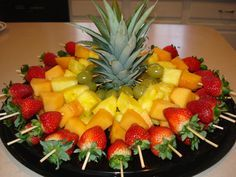 Fruit skewers for a party Cut top off of pineapple to stabilize the skewers while traveling to party