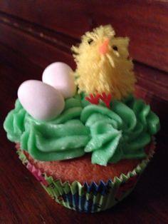 Easter vanilla cupcake with green sugar cream and chocolate eggs