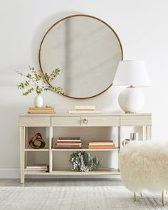 Love this simple all-white entryway look with a tiered console table, sheepskin ottoman and oversized round mirror!