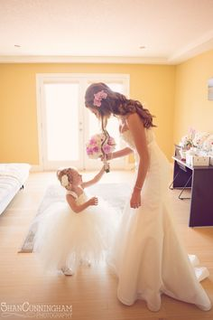 Cute flower girl photo with bride and flowers. Cute flower girl tulle dress.