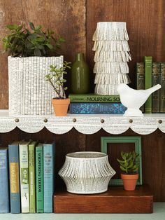 "Simple Scallops on bookshelves:  For beautiful shelf edging, punch 4""-diameter circles from book pages. Fold each one in half, and overlap them along a shelf edge, using upholstery tacks to secure."