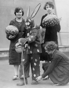 An Easter bunny carries eggs in a basket on his back while posing with women. c. 1930