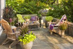 Ipomoea, Pennisetum, Lobularia, Euphorbia y Supertunia, combinados en grandes macetones, decoran este acogedor patio.