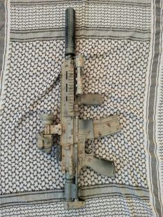 The Heckler and Koch HK416C. Quad rail, vertical foregrip, red dot sight, suppressor, flashlight, telescoping stock, all powdercoated with an unknown camo pattern. Quite a sweet little package!
