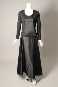 A striking two piece evening dress from Geoffrey Beene is done in a combination of black wool jersey and black satin. The center part of the top and the entire skirt are made from the satin. The rest of the top is jersey. The skirt is finished with a wide band of horsehair at the hemline.