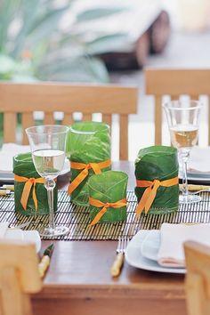 Enrolados em folhas colhidas no jardim (estas são de antúrio), cilindros de vidro, como copos de uísque ou long drinks, tornam-se lindas luminárias para um encontro de fim de tarde ao ar livre. Uma bela fita de gorgorão dá o toque final