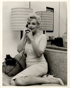 """Vintage original 8 x 10"""" (20 x 25 cm.) black-and-white double weight glossy silver gelatin print still photo, USA. Wonderful still of a lovely and seemingly vulnerable Marilyn deep in phone conversation. From her appearance it is likely that this image was taken during the 1956 filming of PRINCE AND THE SHOWGIRL. The image has rarely, if ever, been seen. There is a stamped inventory number of """"5 2312"""" on the verso. NEAR MINT."""