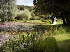 Bride & Groom walking away amongst beautiful water garden scene