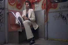 """In the movie """"Saturday Night Fever"""", starring John Travolta, there is a scene that shows the art of graffiti. He is riding the subway and it is evident that the inside of the cart is covered in tags and sayings. Foxy Brown, Katharine Hepburn, Robert Redford, John Travolta, Charlie Chaplin, Den Of Geek, Saturday Night Fever, White Suits, Great Movies"""