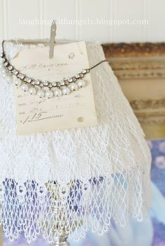 A favorite necklace on a lace-covered lamp shade.  @Laughing with angels