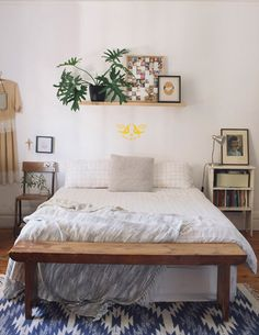 shelf over bed with plant, wooden bench, chair side table, simple rug. via littlegreenshed - lifestyle & family adventures blog