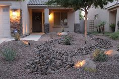 Low Maintenance front yard desert landscape design with rock, river bed, and desert plants...